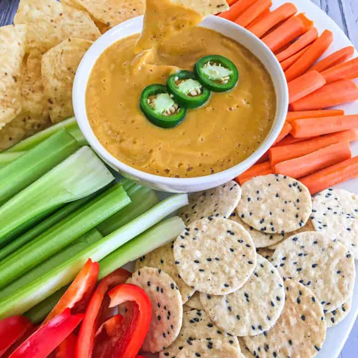 hand dipping chip into jalapeno popper dip