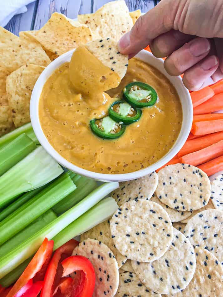 hand dipping cracker into dip