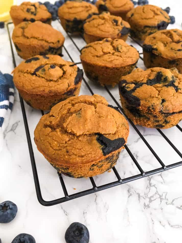 muffins on cooling rack with blueberries scattered around