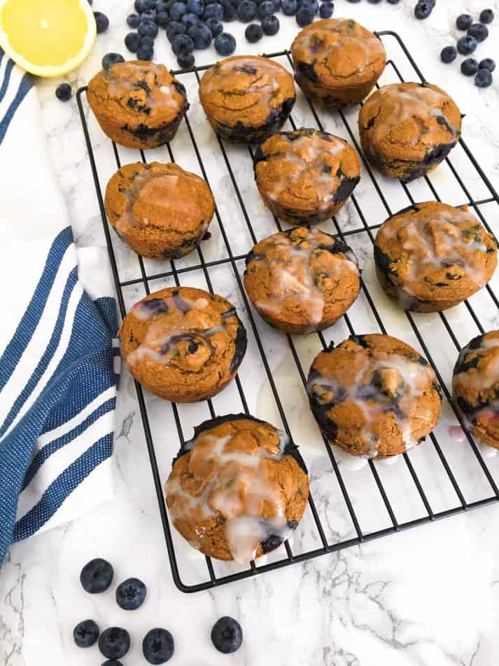 blueberry muffins on cooling wrack with lemon glaze