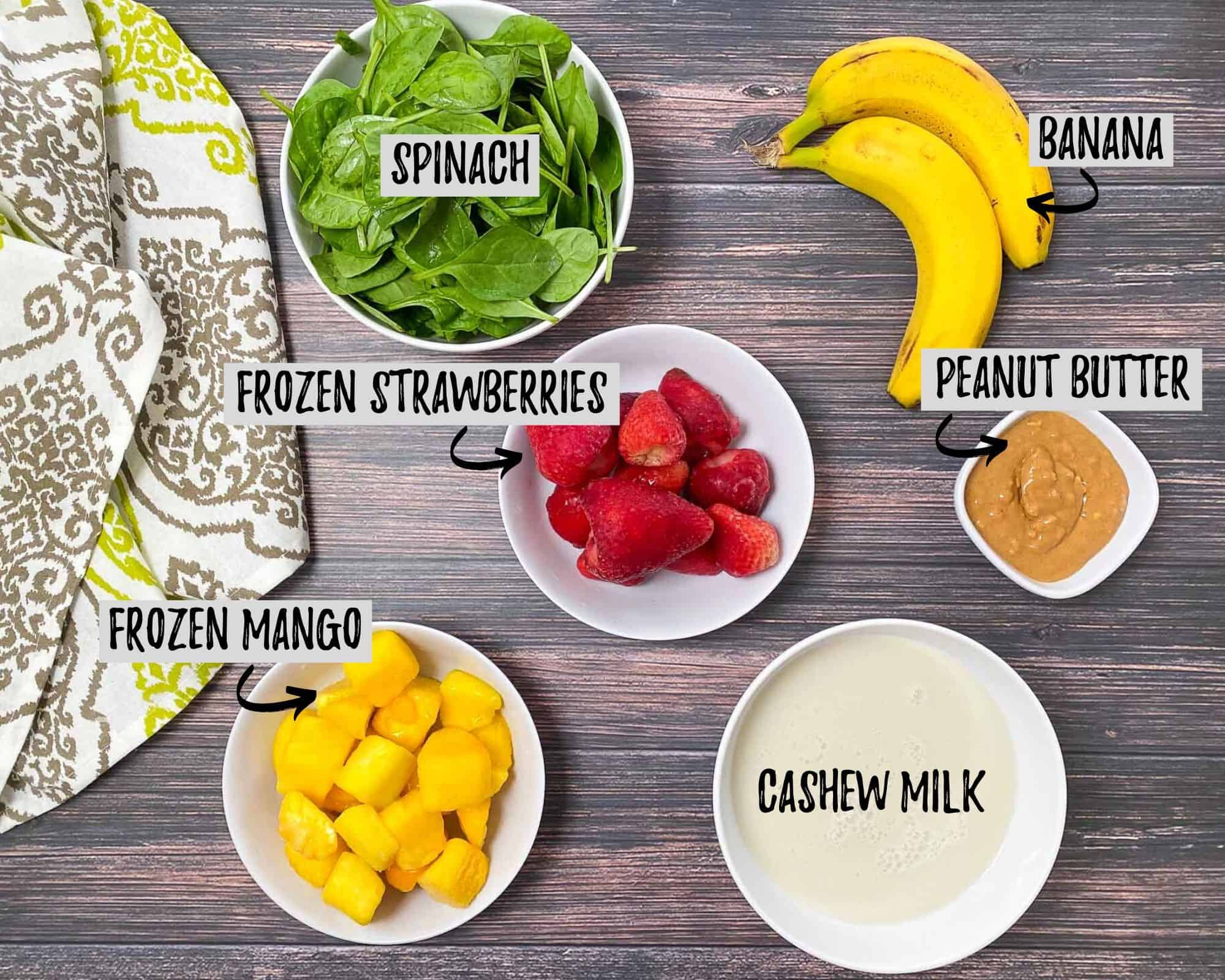 bananas, bowl of spinach, bowl of milk, strawberries, mango and peanut butter on grey deck