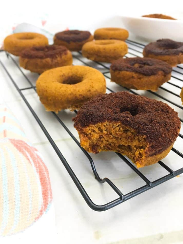 Pumpkin donuts on wire rack with bite taken out of one donut