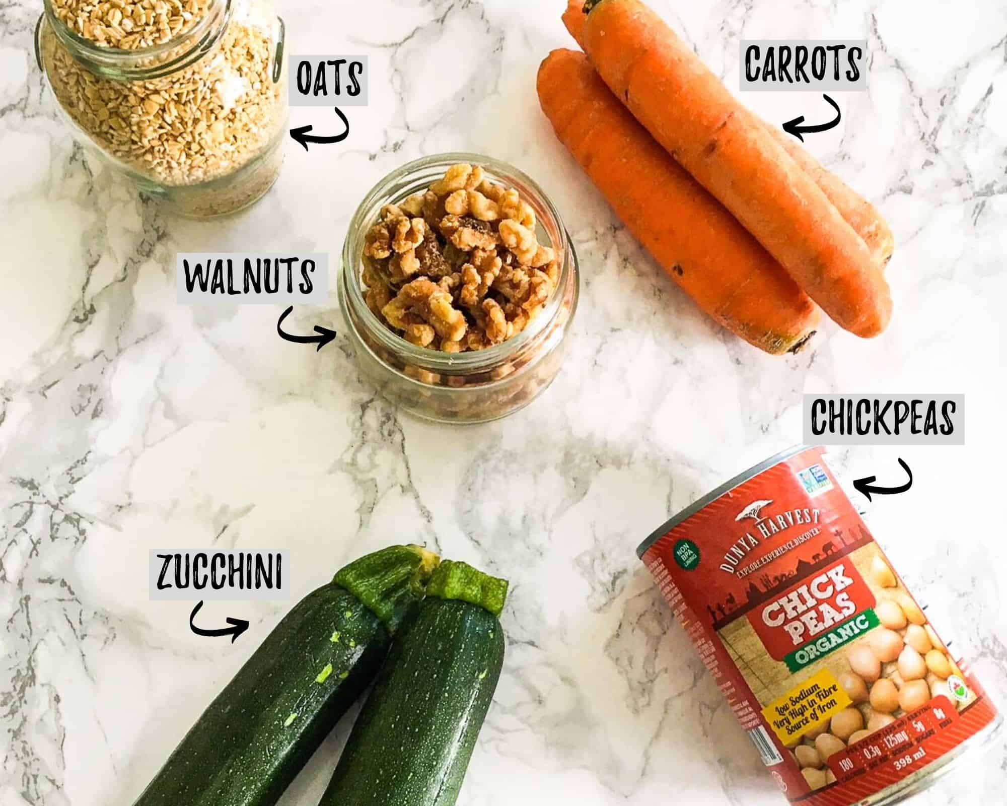 carrots, zucchini, can of chickpeas, jar of walnuts and jar of oats on marble counter