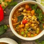 Bowl of soup with sweet potato, mushrooms, zucchini, chickpeas and crushed peanuts and cilantro on top.