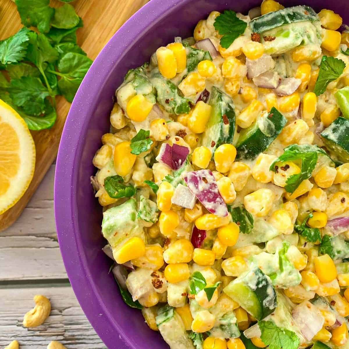 Bowl with corn salad and cutting board with cilantro, cucumber and lemon beside it.