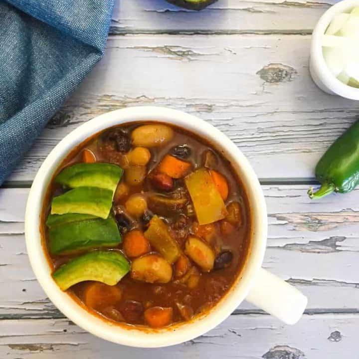 vegan chili in bowl with avocado garnish