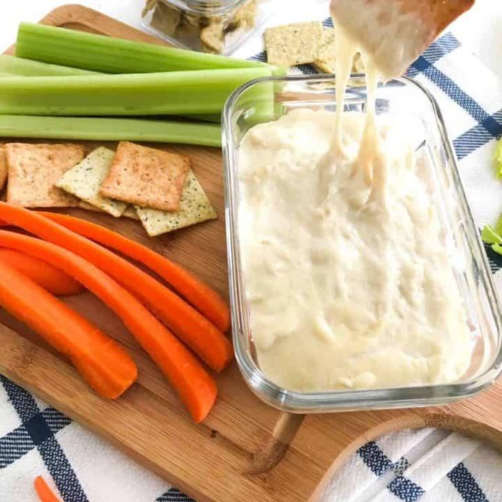 cutting board with celery, carrots, crackers and vegan cheese dip