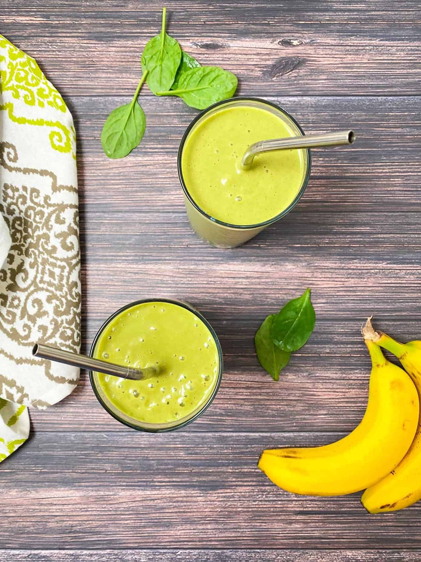 over head view of two glasses of mango spinach smoothies with bananas beside the glases