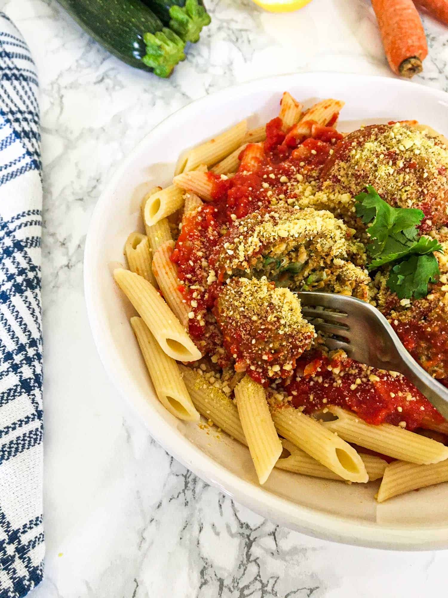 fork cutting through vegan meatball on bed of pasta