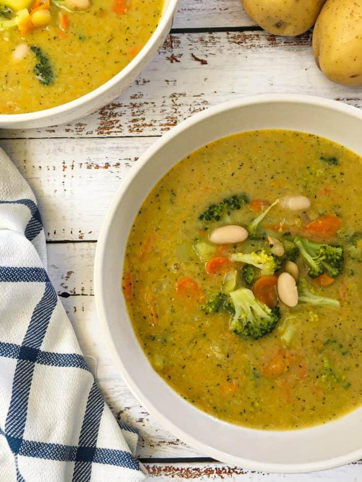 bowl of broccoli potato soup with broccoli, carrot and white bean garnish