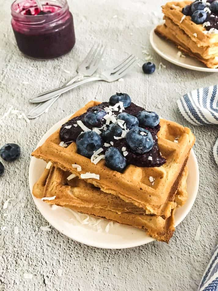 waffles stacked in a plate with blueberries and coconut on top