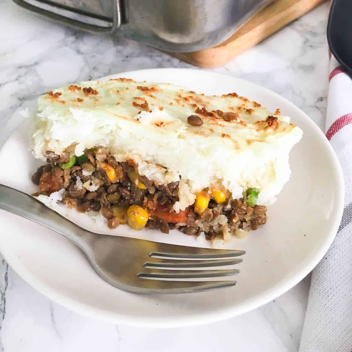 slice of lentil shepherd's pie in plate with fork.