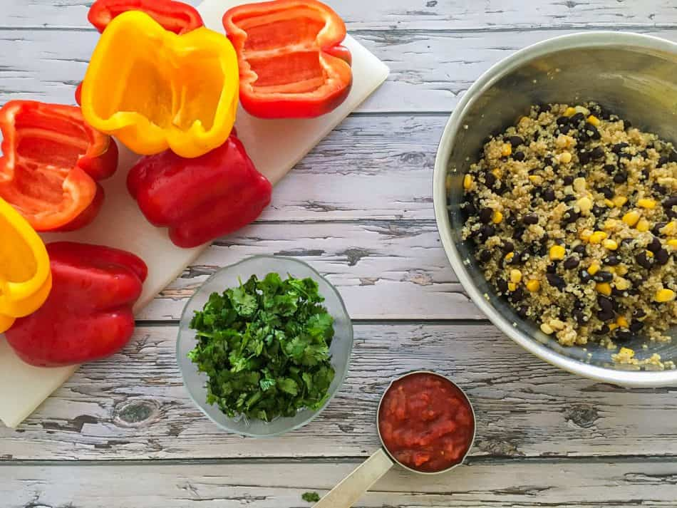 bowl of quinoa, corn and black beans and halved peppers on cutting board