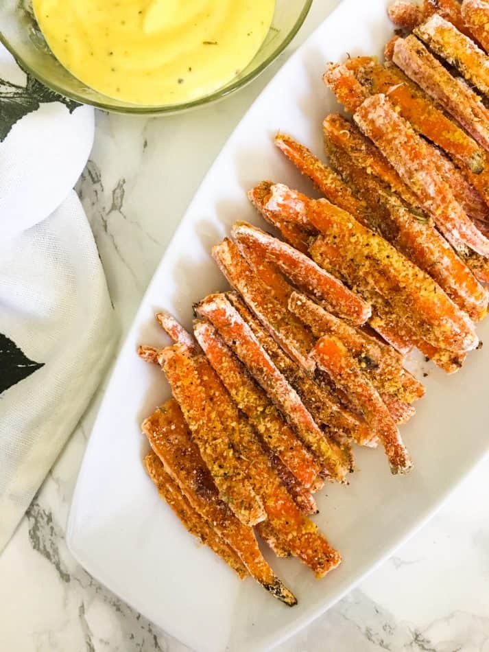 carrot fries on white dish with bowl of dipping sauce beside