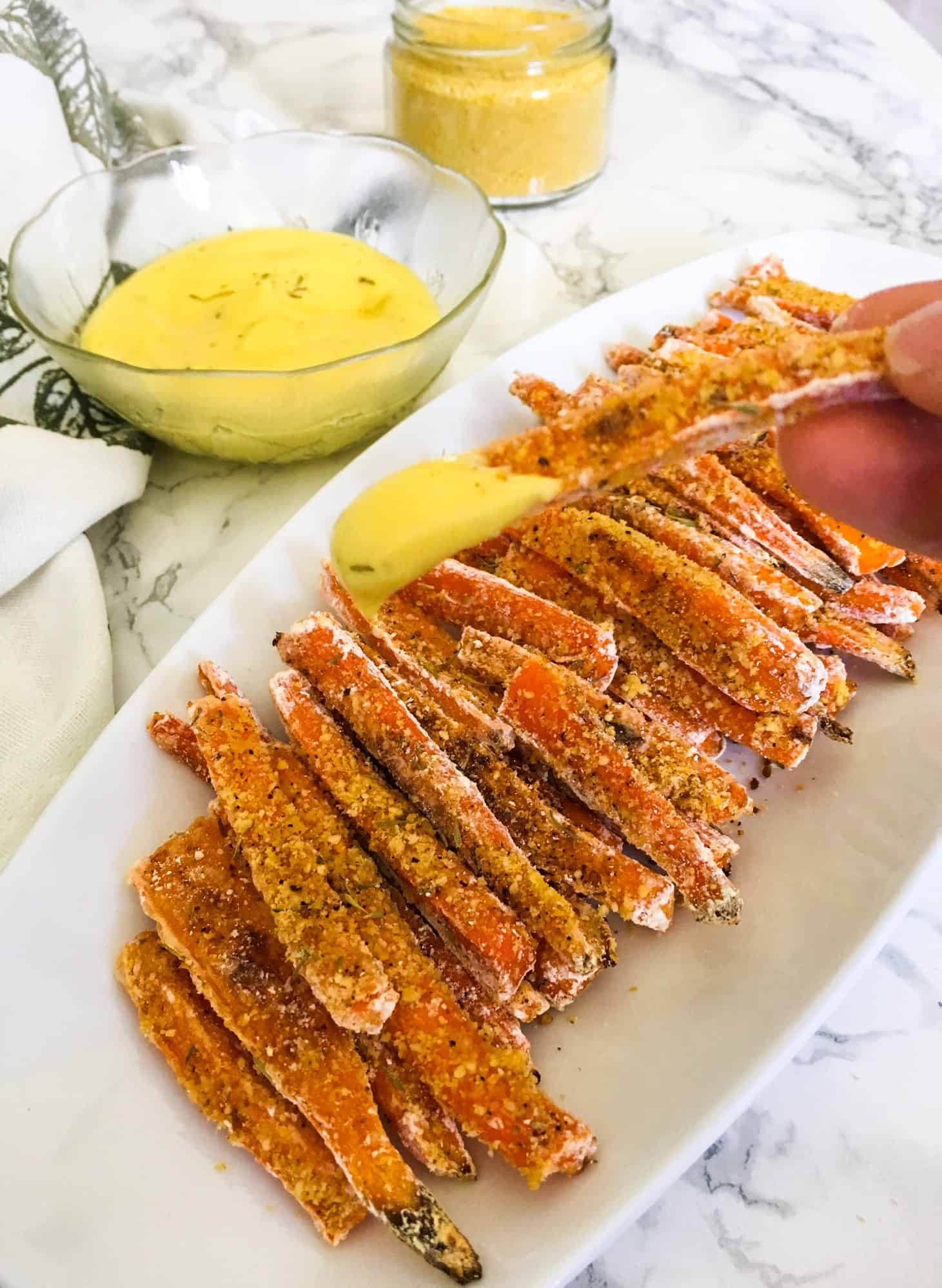 hand holding up carrot fry dipped into dijon mayo sauce