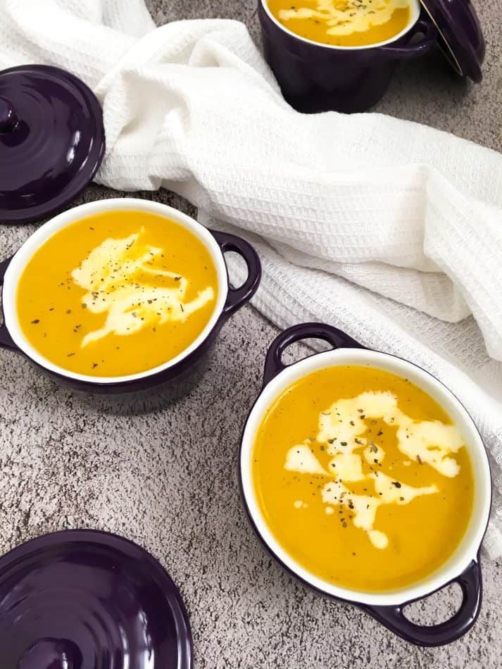 soup in purple bowls with vegan sour cream garnish