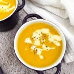 vegan butternut squash soup in bowl with cream garnish