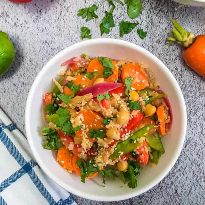 cauliflower rice with snow peas, carrots, red pepper, red onion in bowl