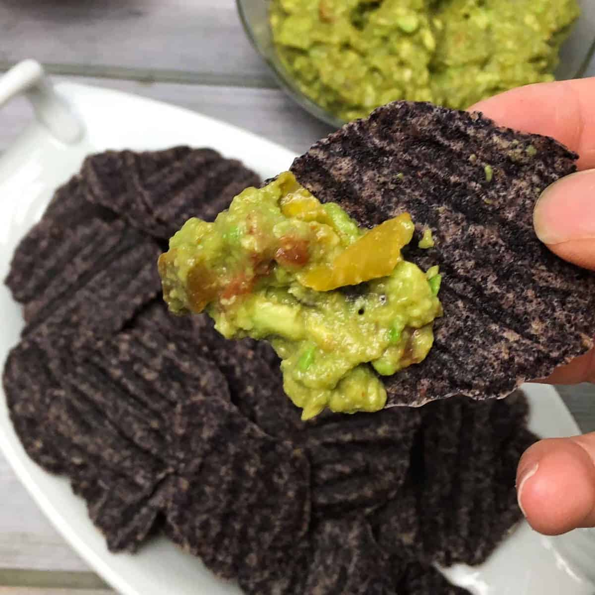black bean chip in hand dipped in guac