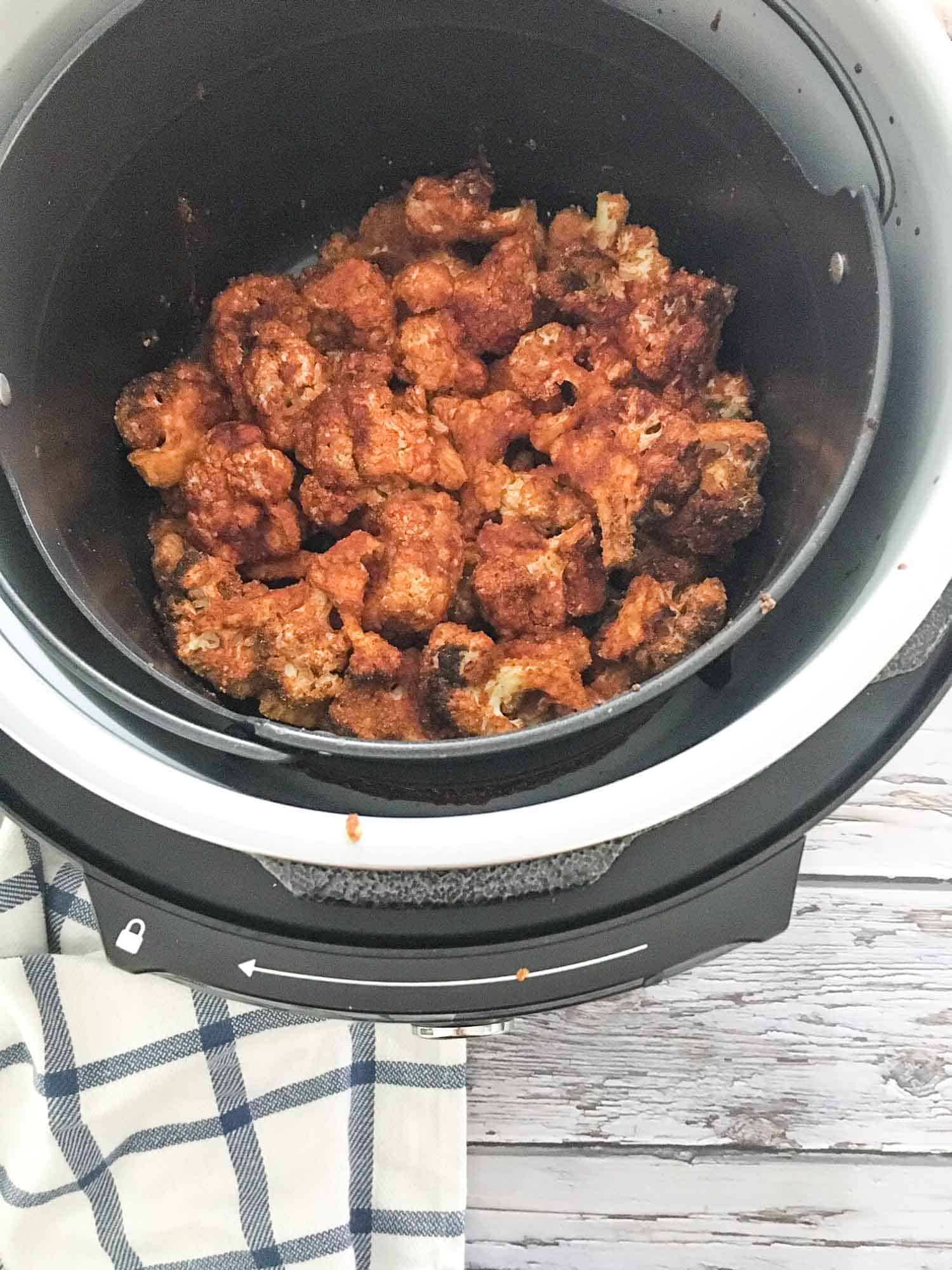 Cooked cauliflower florets that are red and covered in buffalo sauce inside air fryer basket.