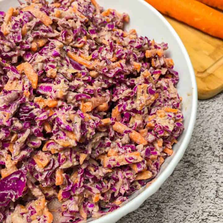 close up of white bowl with vegan coleslaw