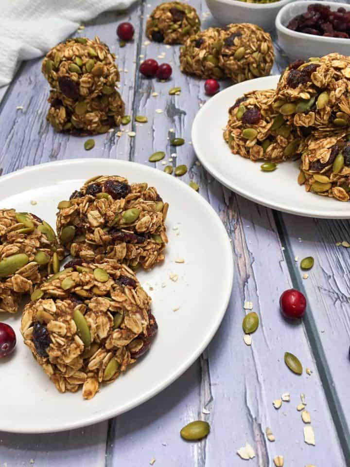 two plates of oatmeal cookies with cranberries and pumpkin seeds scattered around