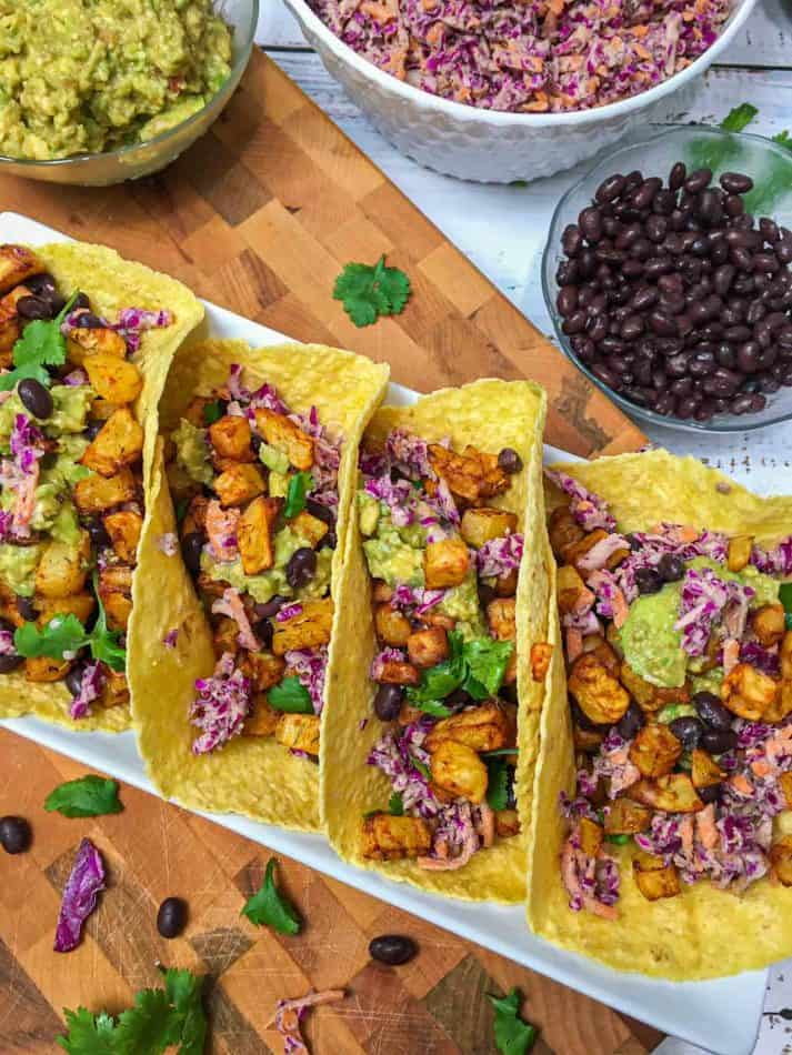 four tacos with potatoes, beans, coleslaw and guacamole in serving dish