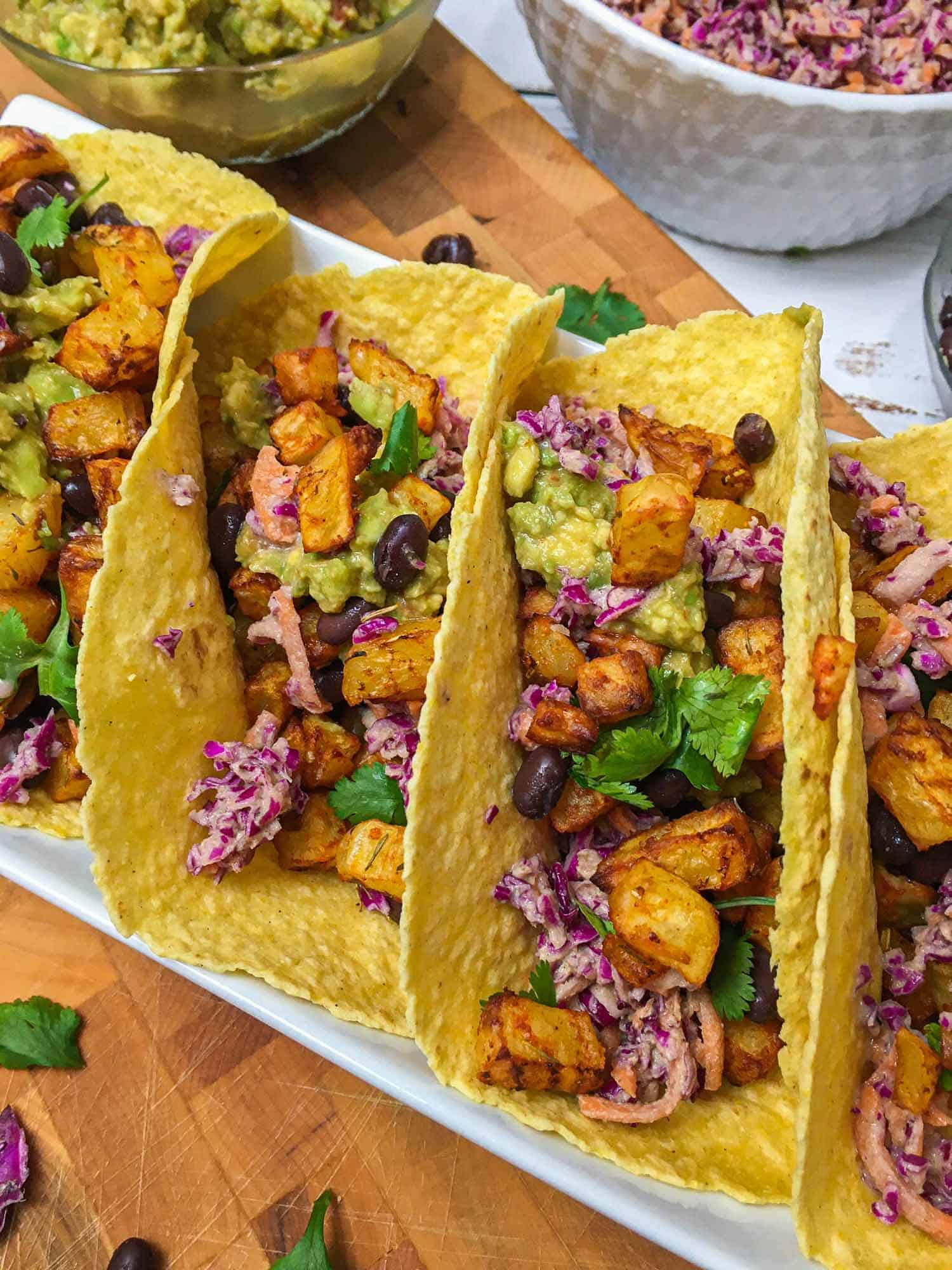 Close up of tacos filled with potato, guacamole, black beans, cilantro and slaw.