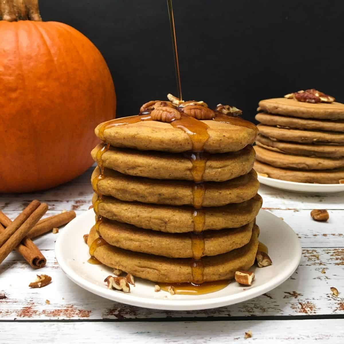 stack of pumpkin spice pancakes in plate with pumpkin in background.