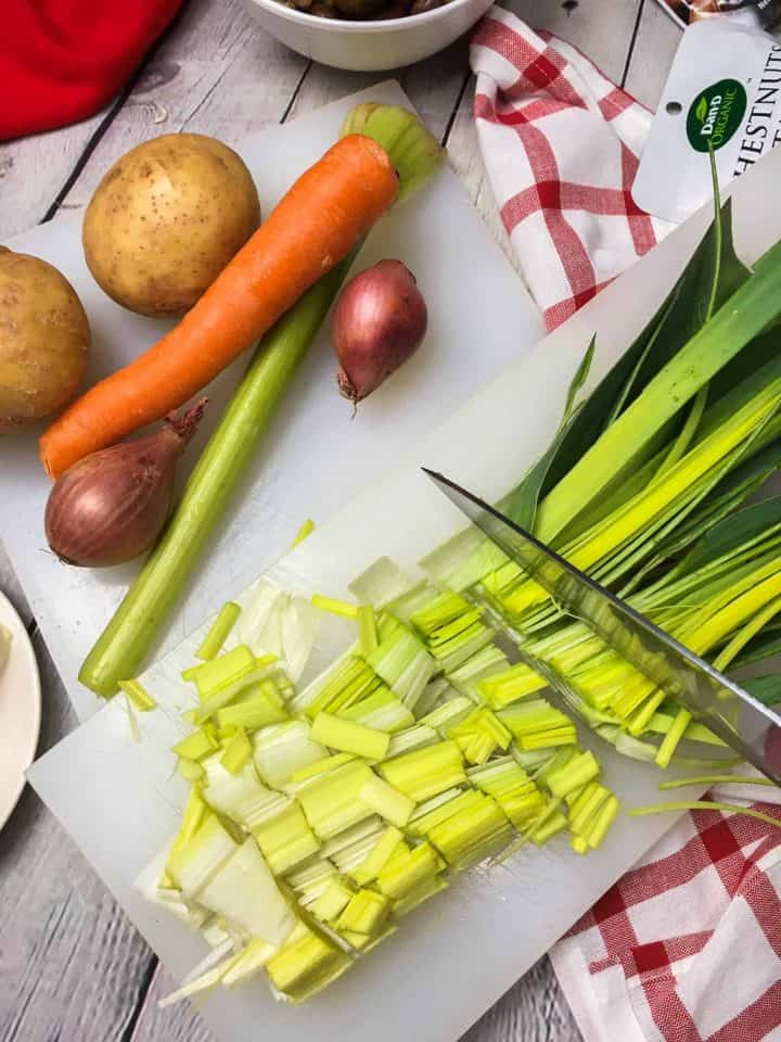leeks quartered lengthwise and being sliced on cutting board