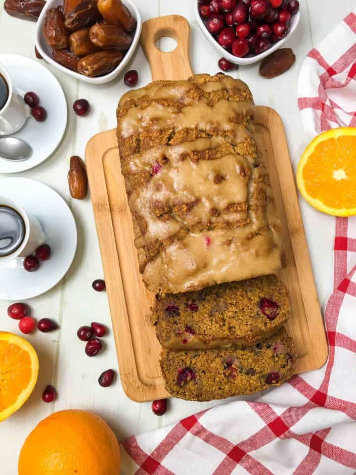 orange cranberry bread on cutting board with two cups of coffee beside it