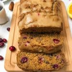 orange cranberry loaf on cutting board with two slices leaning forward