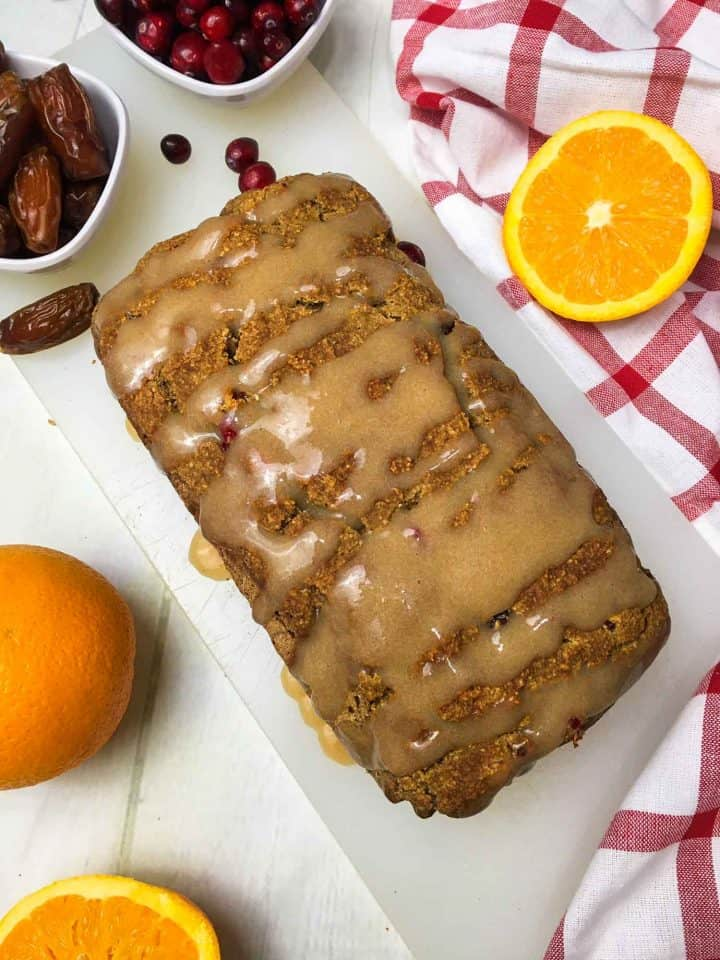 baked orange cranberry bread on cutting board with orange glaze