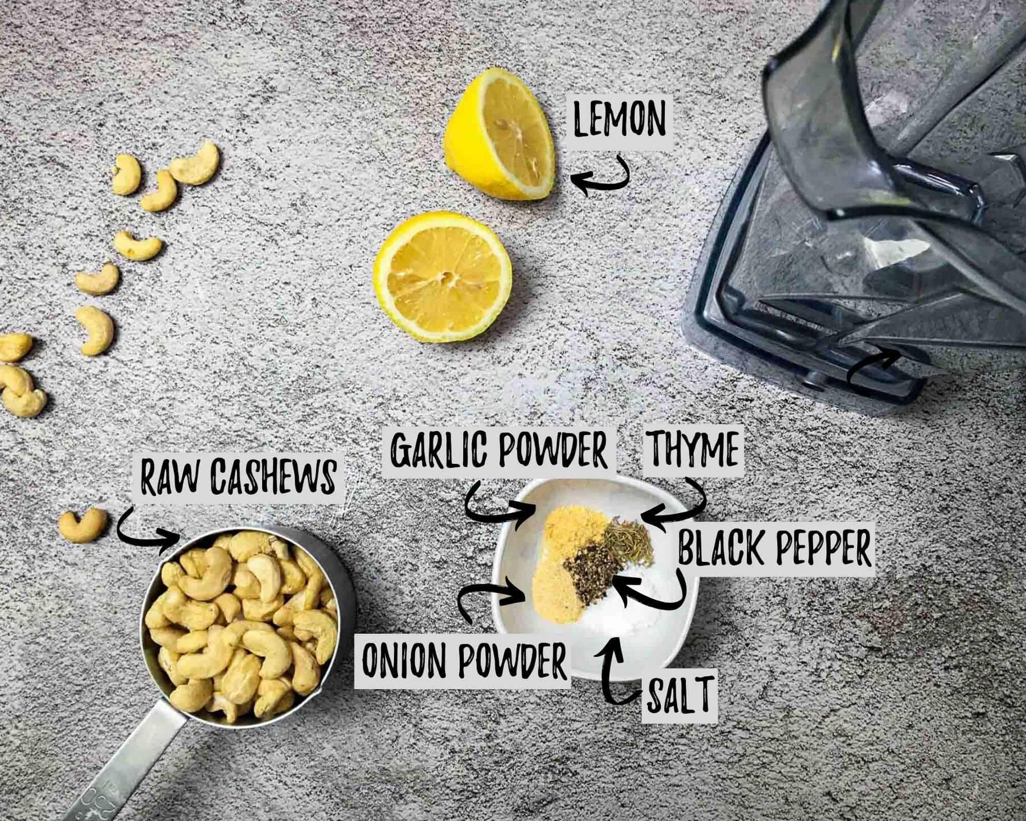 cashews, lemon cut in half and bowl of seasoning on concrete surface