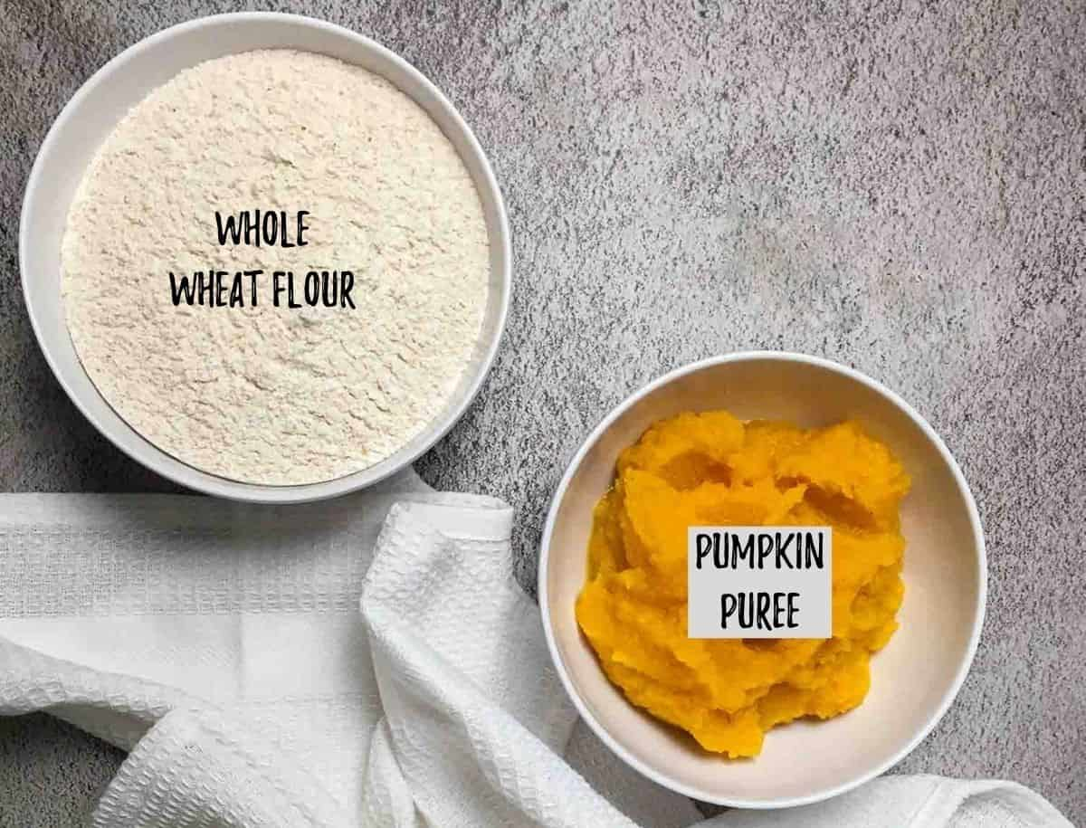 Bowl of flour and bowl of pumpkin puree on counter.