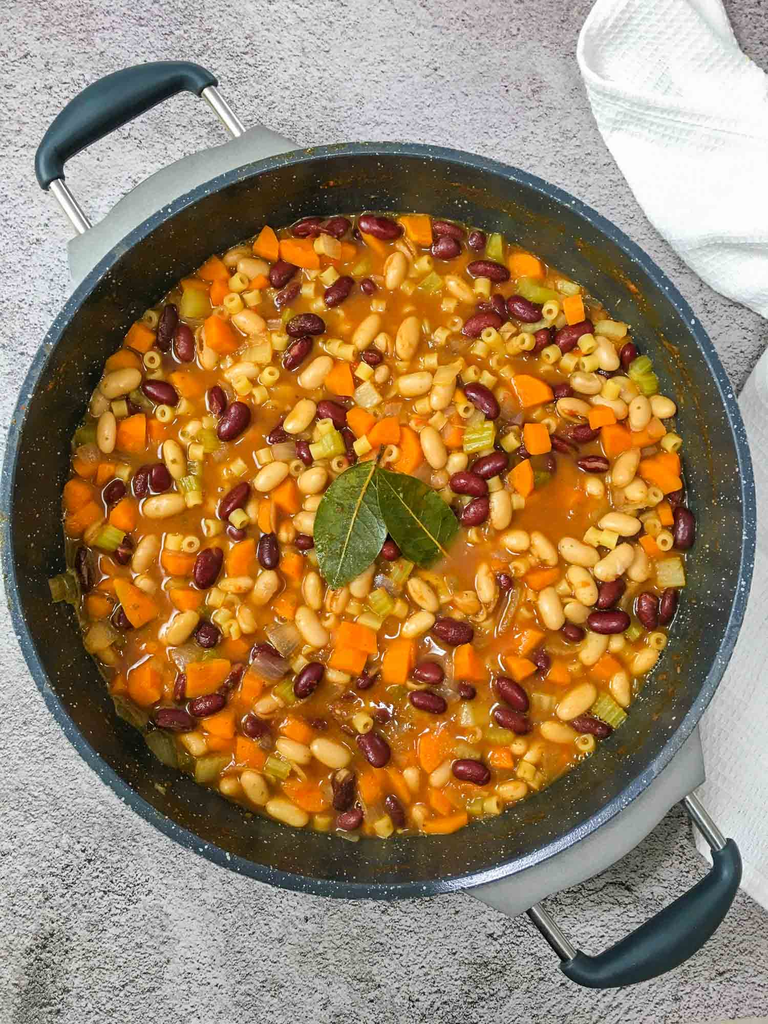 large deep skillet with pasta e fagioli with bay leaves in the center