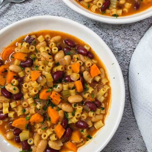 two bowls of pasta e fagioli with parsley garnish