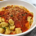pumpkin gnocchi in bowl with tomato sauce on top