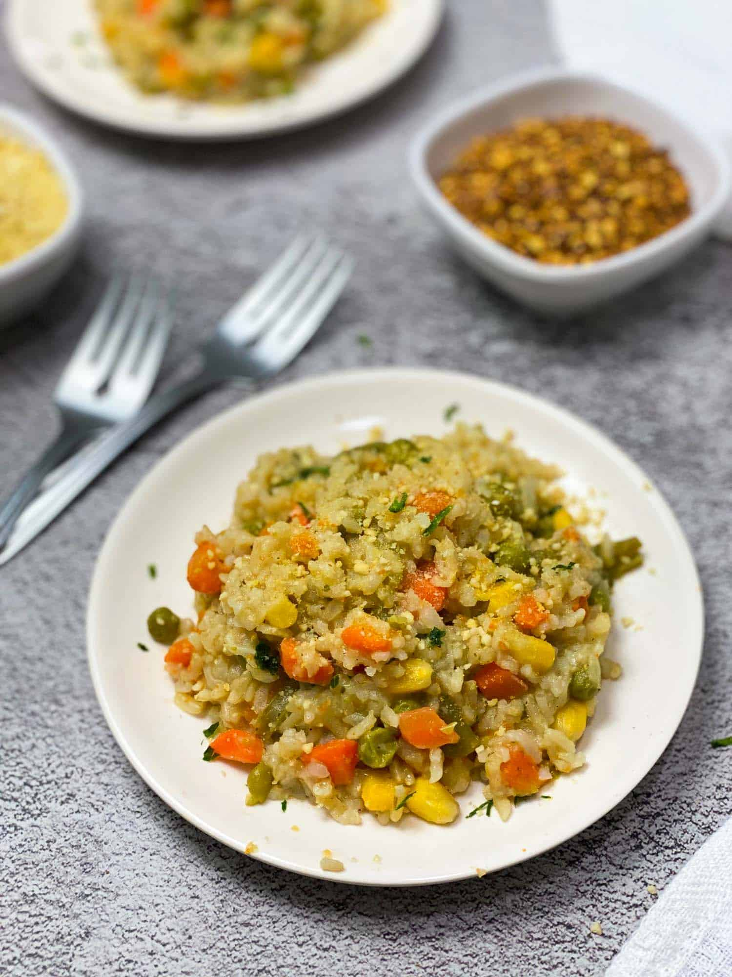 vegan risotto in white plate with mixed vegetables