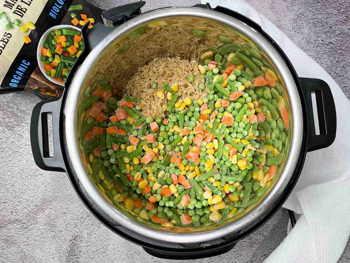 instant pot with raw brown rice and frozen veggies inside