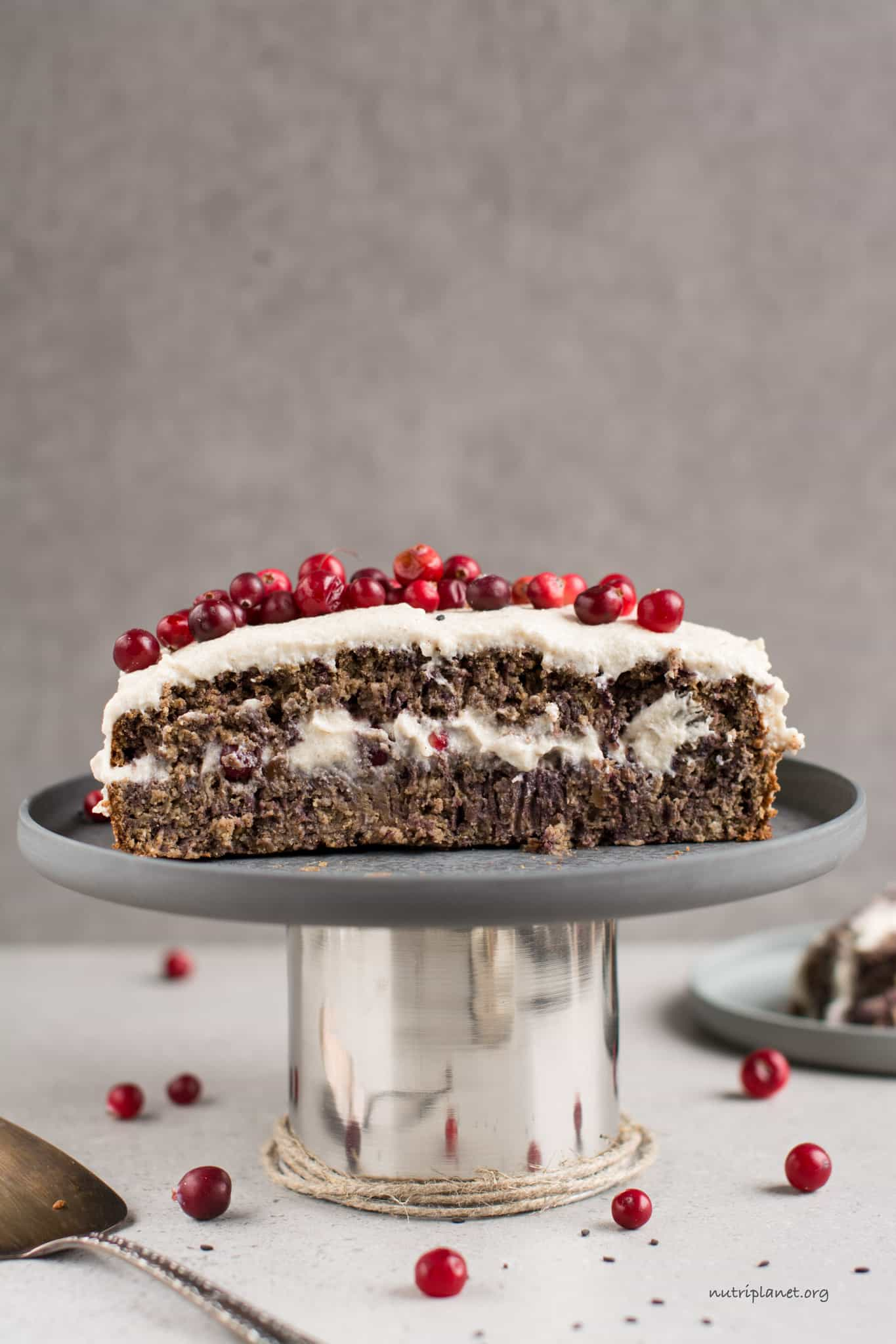 Carrot cake cut in half on cake plate with cranberry topping.