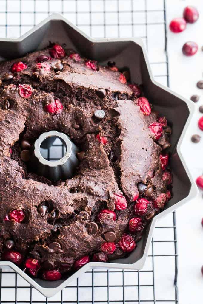 Chocolate bundt cake in bundt pan with cranberries on top.