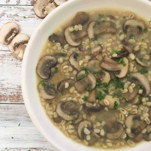 bowl of mushroom barley soup with parsley garnish
