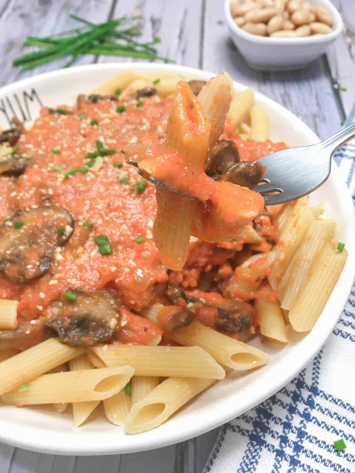 fork full of penne pasta with vegan vodka sauce