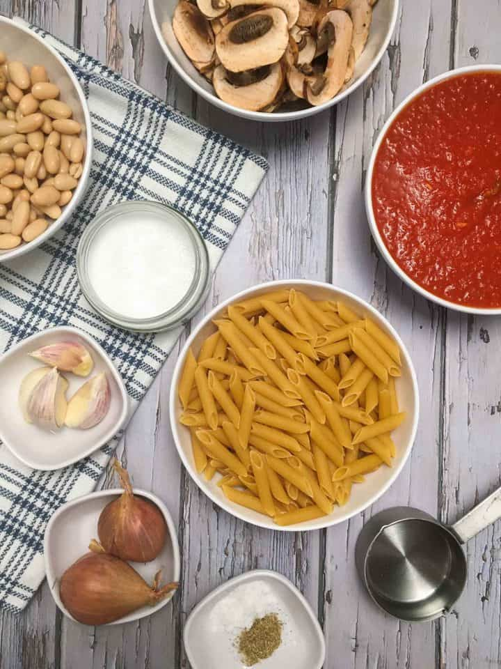 bowl of dry penne pasta, bowl of tomato sauce, cup of coconut milk, cloves or garlic and shallots in bowls