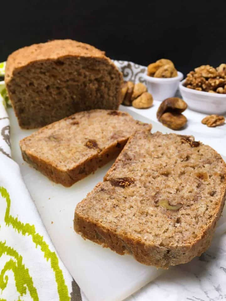 sliced whole wheat fig and walnut bread on cutting board with loaf in background