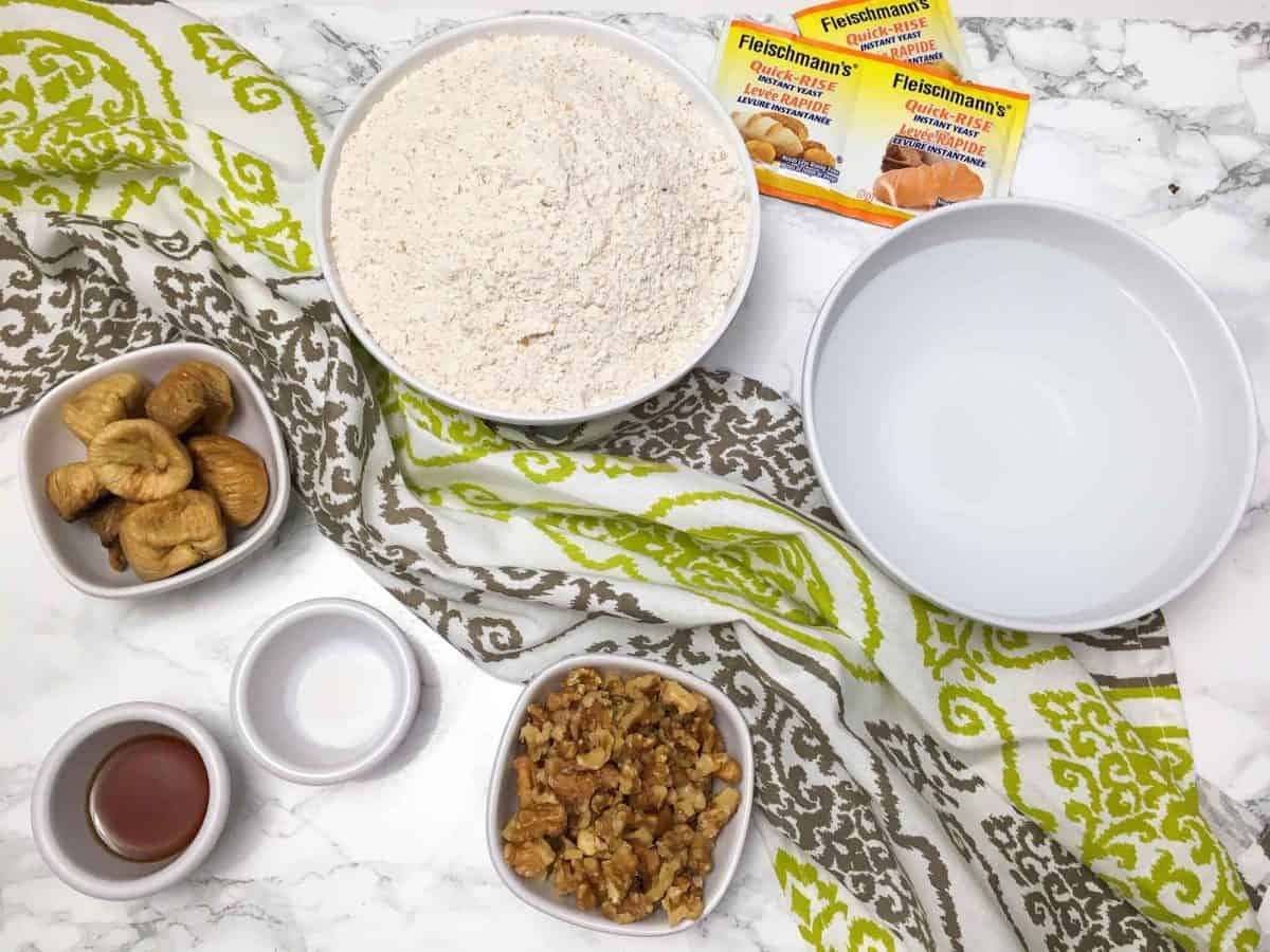 bowls of flour, water, walnuts, figs on marble counter