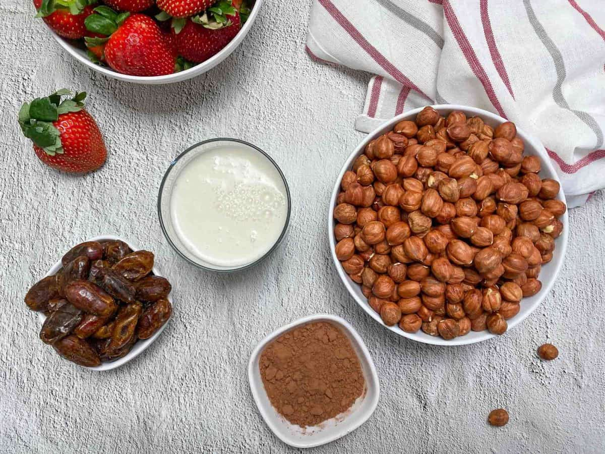 bowl of raw hazelnuts, cocoa powder, milk, dates and strawberries with white, red and grey towel in background