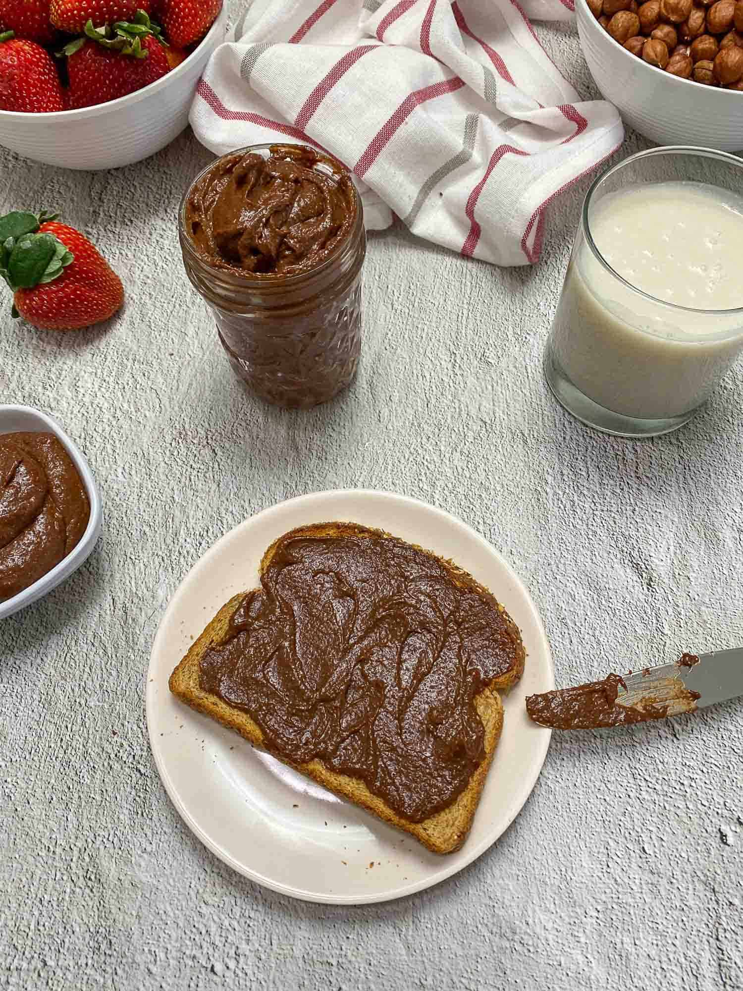 nutella spread on toast with glass of milk in background