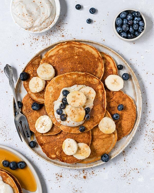plate of pancakes with sliced bananas and blueberries on top
